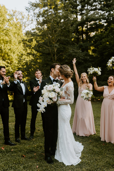 adeline waugh bride and her groom kiss while their wedding party cheers them on at the woodend sanctuary in bethesda maryland