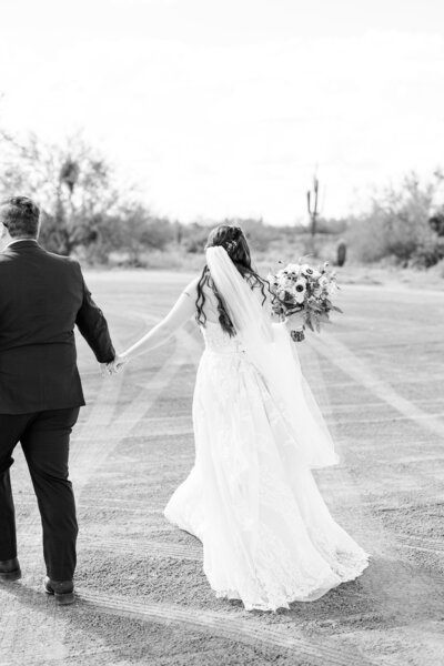 A groom leading his bride across the desert on their wedding day