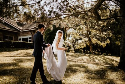 Newlyweds walking groom holding brides dress