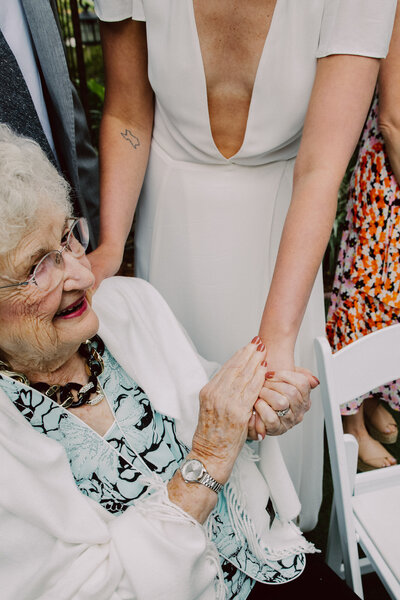 A grandmother holding her granddaughters hand