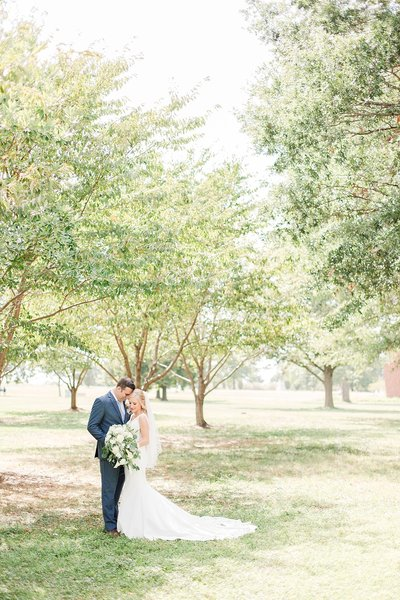 bride and groom hugging in park at bayfront club wedding by costola photography