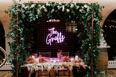 Wedding reception head table with flower arch and unique neon sign