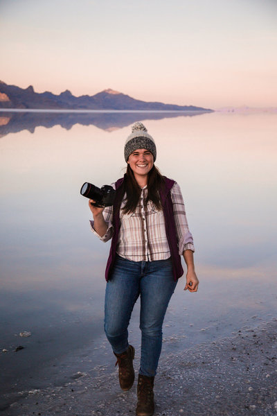 Photographer wearing a pink plaid shirt and jeans stands next to the Utah Salt Flats. The flats are covered with a thin layer of water making the surface reflect the sunset and mountain range in the distance.
