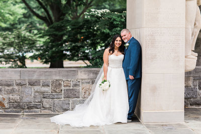 Dark haired bride in wedding gown with groom in navy suit leaning against wall