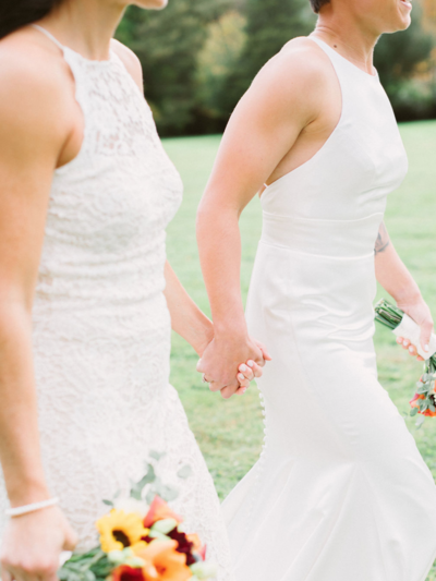 Brides holding hands in backyard wedding in Massachusetts