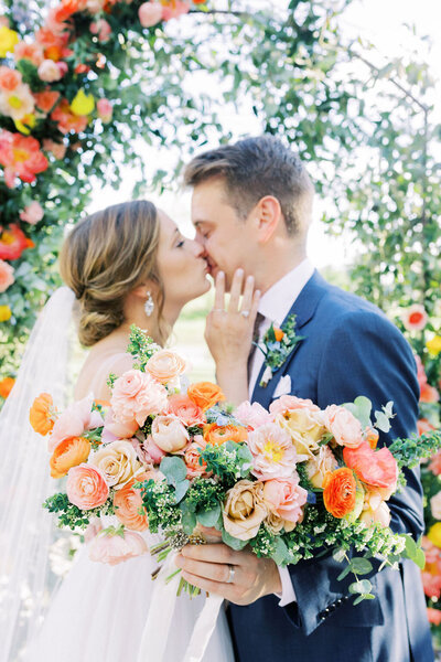 bride and groom share a kiss in front of a spring and colorful floral arch in cincinnati ohio groom is wearing a navy suit and holds the bridal bouquet thats orange pink peach and cream made by cincinnati wedding florist roots floral design