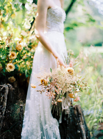 Textural bouquet with golden flowers and dried grasses for a romantic boudoir session