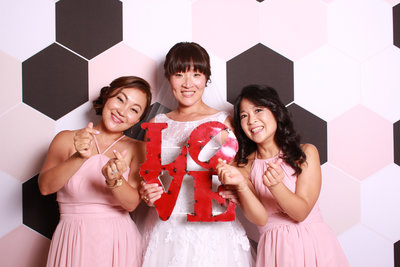 Bride and bridemaids holding a love sign as prop while taking photos