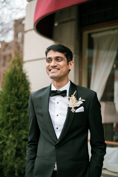 indian groom grins as he sees his bride walk towards him he is wearing an all dried white boutonniere at the brown hotel