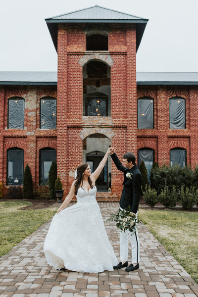 Groom is twirling his bride in front of the Providence Cotton Mill photographed by Charlotte wedding photographer, Stephanie Bailey Photography.