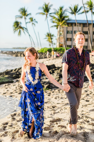 Couple walking on a beach in Hawaiii. Blue floral Lulus dress and leis. Palm trees and Lava rocks in the background