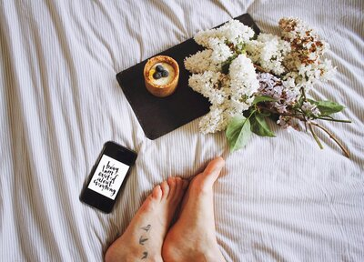 Flatlay of a cellphone and bouquet of flowers in bed