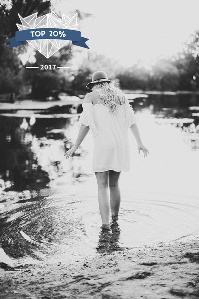 Senior girl in a white dress walking into a pond