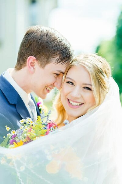 Bride and groom touching foreheads with colorful New Hampshire bouquet