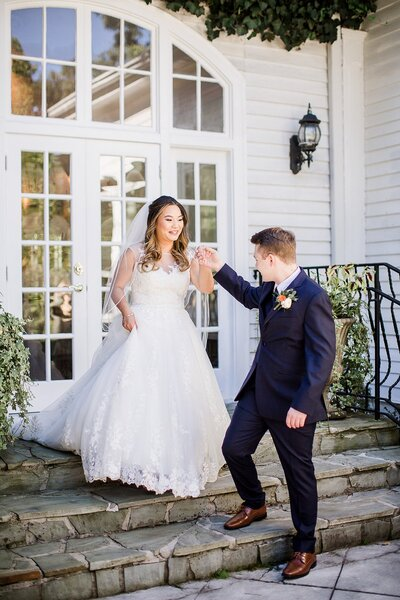 Groom helping bride walk down stairs by Knoxville Wedding Photographer Amanda May Photos