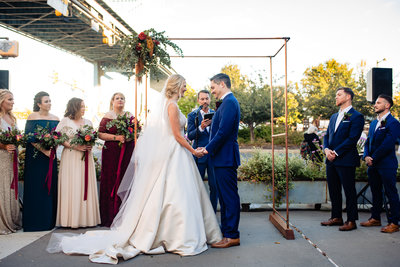 Bride and groom standing in front of arch at wedding ceremony with flower arrangement in the corner of copper rods