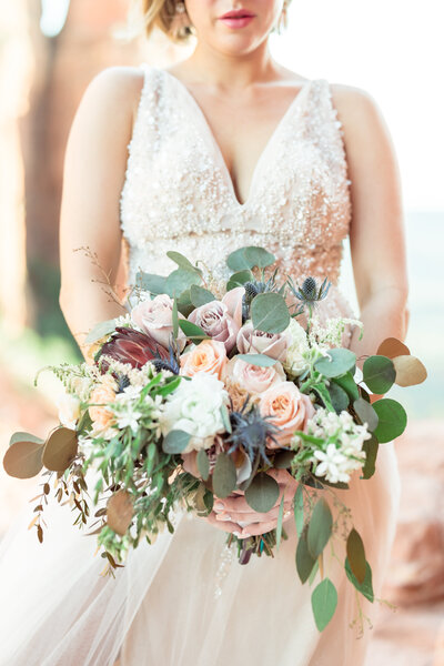 A stunning bride holding a bouquet of eucalyptus and chrysanthemums
