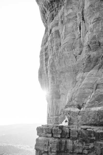 Bride and groom walk along cliff while photographer captures the moment