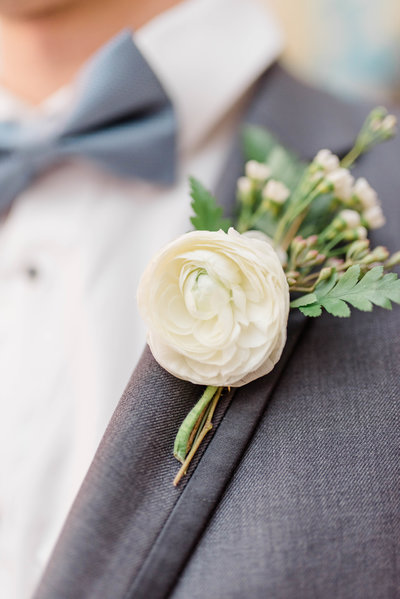 Close up of navy groom's tux with white floral boutonnière