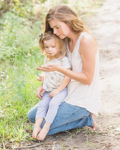 daughter sits in moms lap as they look at a wildflower