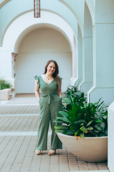 The Holistic Mrs founder, Rachel Newton, in beautiful green jumpsuit under architectural arches in San Francisco Bay Area