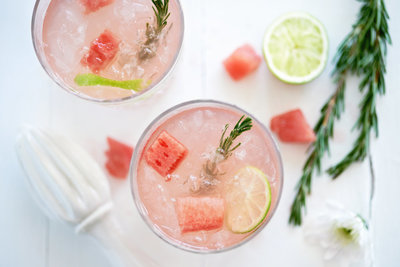 Specialty cocktails garnished with watermelon, rosemary, & lime