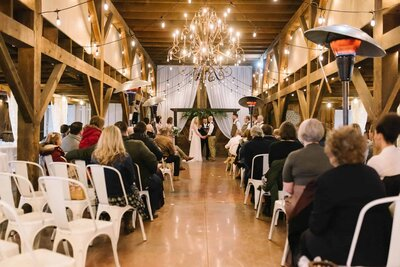 Indoor barn wedding ceremony with chandelier
