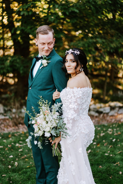A bride and groom where the bride is holding a flower bouquet and the groom has a flower boutonniere