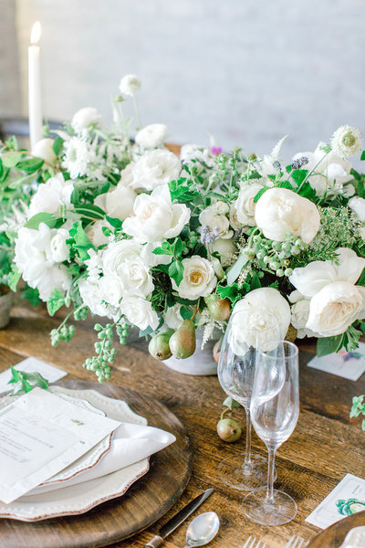 a farm-to-table inspired tablescape with rustic wood charger plates and a lush white floral centerpiece with accenting candles