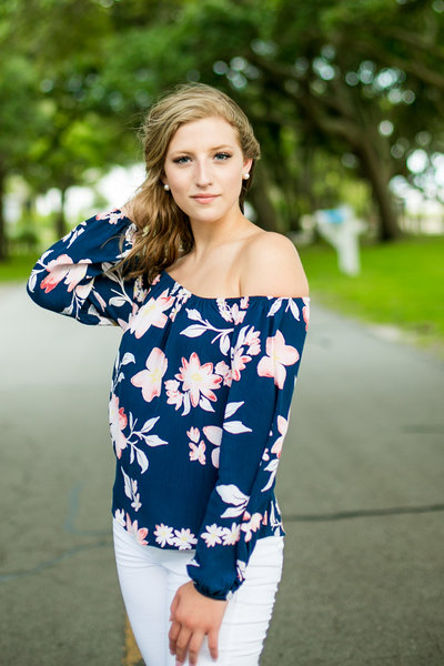 Teenage girl in floral blouse poses outside for senior photography session
