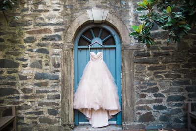 M. Harris Studios - Wedding Gown Hanging on Blue Door on Stone Wall