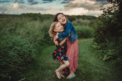 Two young girls hugging and laughing at Country Cut Flowers in Newmarket at sunset