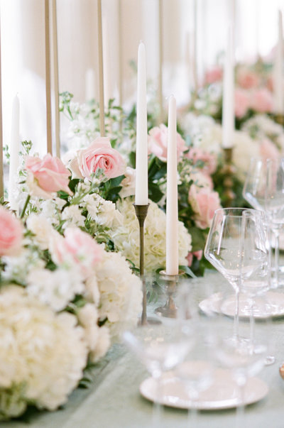 Wedding reception table with floral running, candlesticks, and place settings