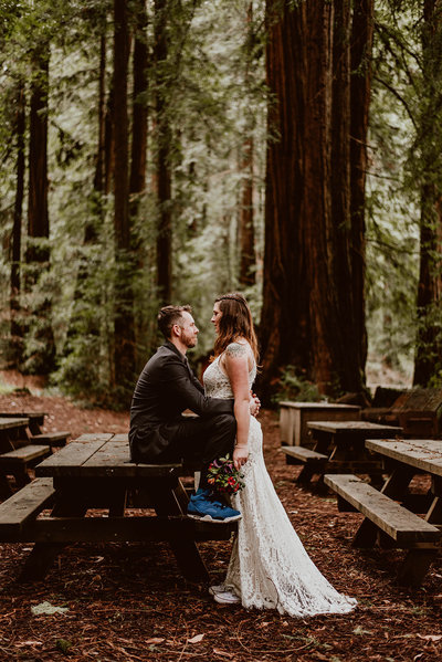 Couple gazes at each other leaning against a picnic table in a redwood forest
