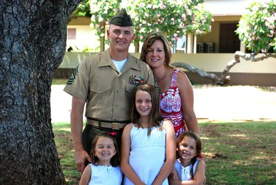 Marine and his wife and 3 daughters pose for family photo