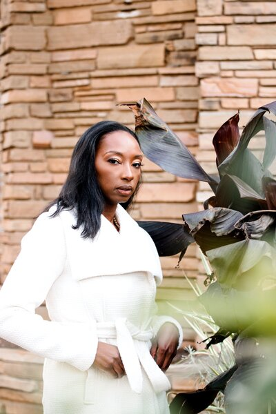 Modern brand shoot with  woman in white coat behind plants