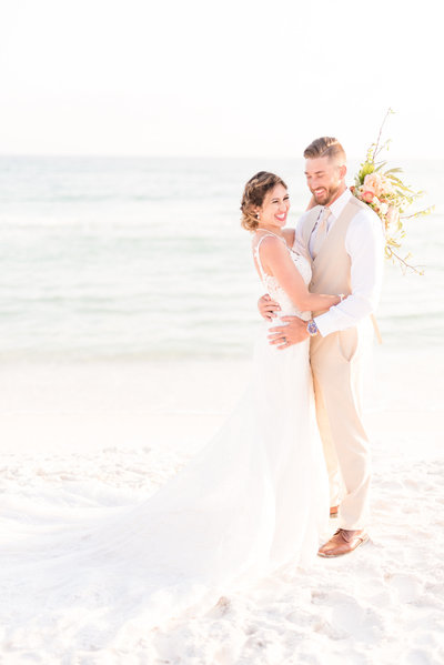 Bride and groom laugh together on beach.