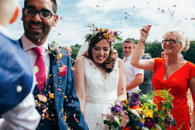 Smiling bride and groom during confetti throw photograph at The Boathouse in Ormseby, Norfolk