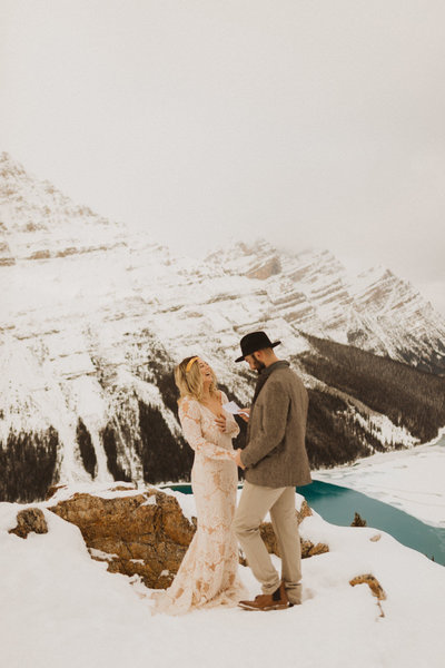 couple reading their vows at Peyto Lake on the edge of the mountain
