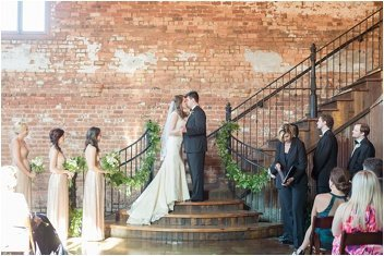 wedding ceremony first kiss at the Old Cigar Warehouse in Greenville