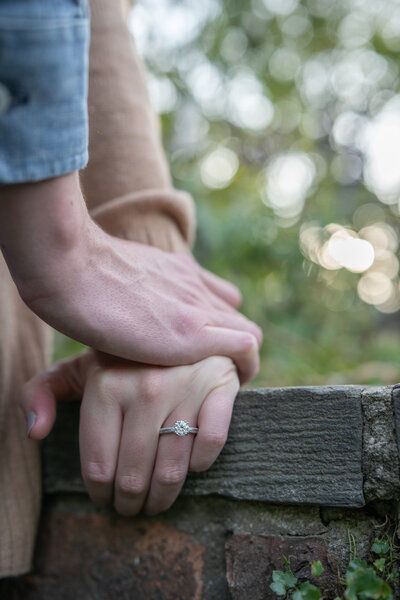 holding hands on a ledge with an engagement ring