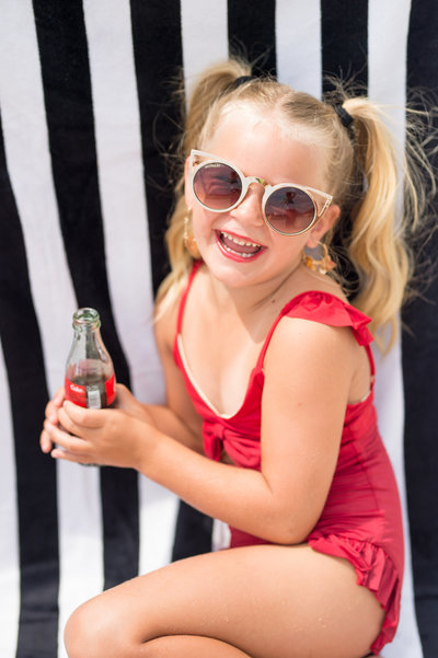 Child in a red swimsuit holding a can of coke