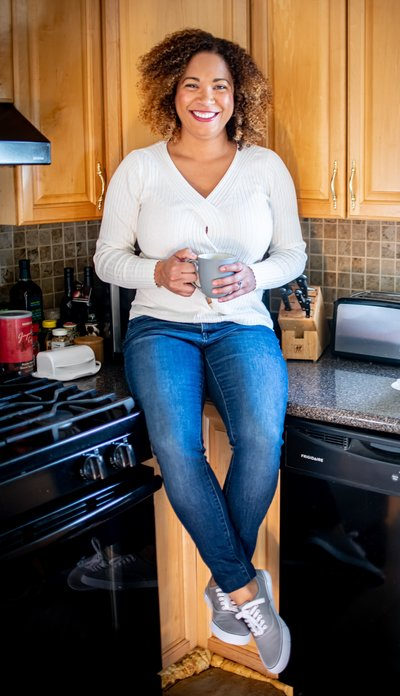 woman sitting on a counter top in a kitchen smiling and holding a cup of coffee