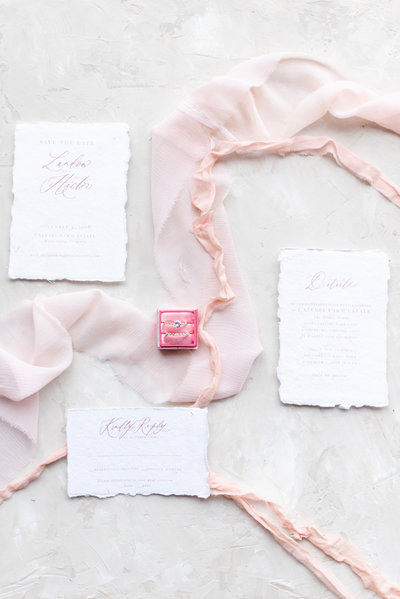 wedding ring in pink box surrounded by pink ribbon and wedding invites flat lay