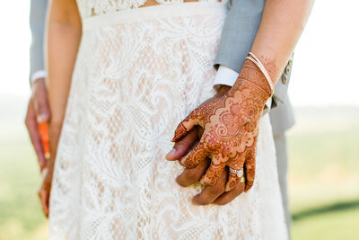 Bridge and groom holding hands with bridal henna in Santa Barbara, California. Photo taken by Cheers Babe Photo..
