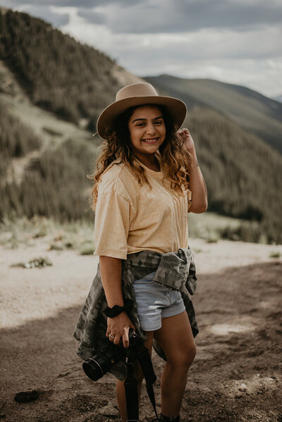 woman smiling on top of a mountain