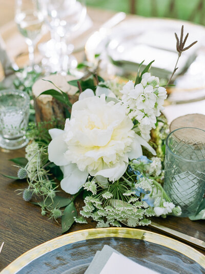 Close up of reception table decorated with large white flower, gold rimmed plates, and glass candles