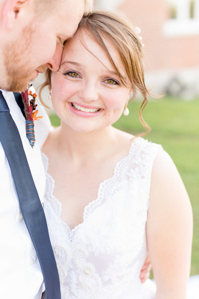 Bride smiles at camera while groom snuggles.