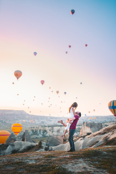 man-carrying-woman-with-hot-air-balloons-background-3889705