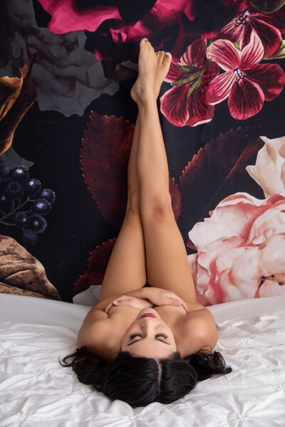 woman laying down on bed with floral backdrop